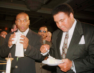 File photo of boxing great Muhammad Ali (R) eating a piece of his birthday cake as boxer Mike Tyson looks on at the MGM Grand hotel in Las Vegas