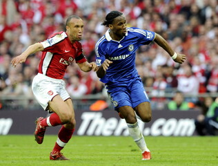 Mikael Silvestre - Arsenal in action against Didier Drogba - Chelsea (R)