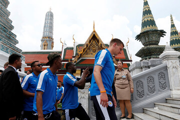 Leicester City soccer club's players walk as they visit the Emerald Buddha temple in Bangkok