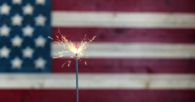 Glowing sparkler with rustic wooden flag of United States of America for labor day, July 4th, Memorial