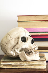 Vintage books in pile with scull open mouth on the shelf