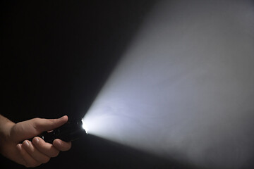 Male hand holding a led flashlight with a very wide white beam on a black background, leaving the left side of the frame