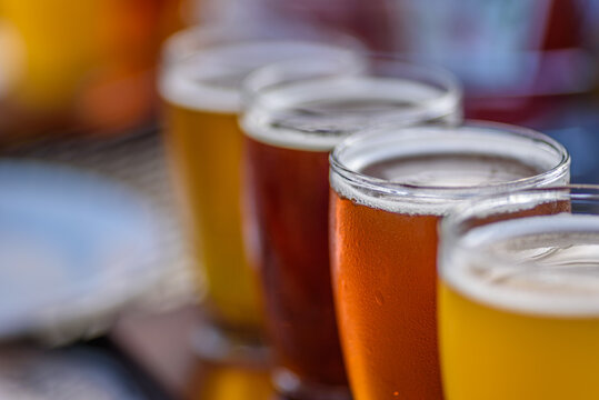 closeup of a beer flight sampler outside at microbrewery in summer sun