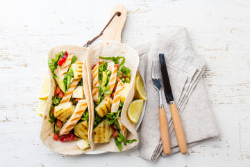 Mexican tacos with grilled chicken and pineapple on wooden background with cutlery