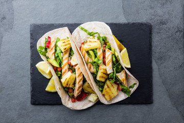 Mexican food. Tacos with grilled pineapple, chicken and vegetables, slate background