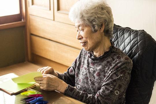 折り鶴を折る笑顔のシニア女性