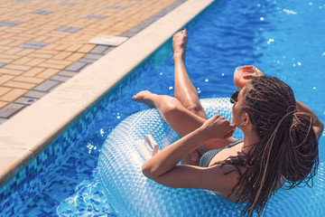 beautiful sexy girl with zizi cornrows dreadlocks lying in swimming circle in swimming pool. Summer vacation and relax concept.