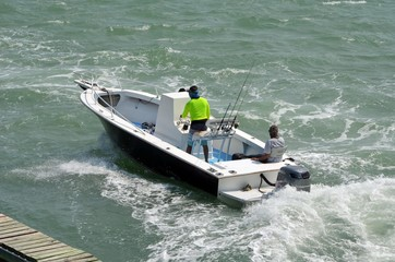 Small open fishing boat powered by a single outboard engine on the florida intra-coastal waterway off of miami beach.