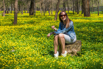 Young beautiful woman in the yellow field in Central park in Almaty, Kazakhstan