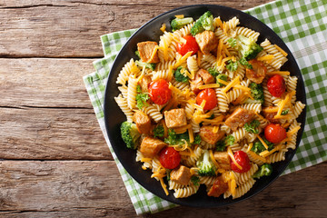 Fusilli pasta with pork, broccoli, tomatoes and cheese cheddar close-up on the table. Horizontal top view