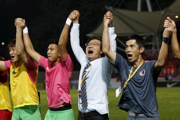 Hong Kong players and coach Kim Pangon acknowledge supporters after drawing against China in their World Cup qualifying match against Hong Kong in Hong Kong, China