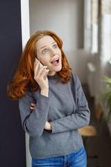 frau telefoniert und schaut überrascht nach oben