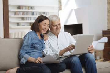 couple using their laptop to pay their bills at home in the living room