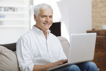 Smiling mature man sitting on a sofa typing on a laptop in a living room