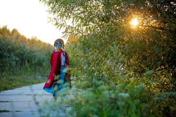 Cute sweet little preschool child, boy, playing superhero on a rural path in a small village