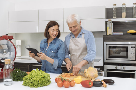 Mature couple cooking meal at home