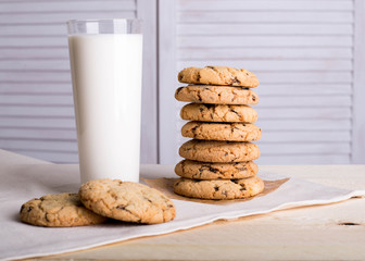 Chocolate biscuits and a glass of milk on a linen towel on a wooden table with a white background. Vintage view. Place for the inscription.