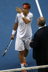 Spain's Ferrer talks with referee McKewen as the roof is closed due to bad weather during his quarter-final match against Britain's Murray at the Australian Open tennis tournament at Melbourne Park
