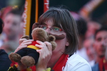 A fan of Germany holds a teddy bear as she watches the Euro 2016 match between France and Germany at a public screening in Berlin