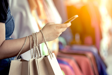 Woman hand holding shopping bags and using smartphone on the street in the shopping mall in vintage color tone