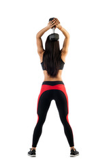 Sporty woman fitness model doing exercise with dumbbells, hands behind head in semi-bent position, rear view on white isolated background. Example exercises with dumbbells