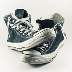 Old and worn pair of sneakers with white background