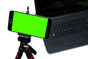 Smart phone on tripod with green key screen record laptop.