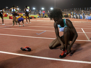 Tori Bowie of U.S takes off her shoes after winning the 100m women event at the IAAF Diamond League athletics meet, in Doha
