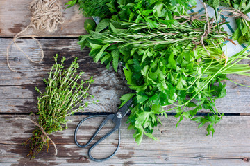 A bunch of fresh thyme on a wooden table with other fresh fragrant herbs, top view, horizontal