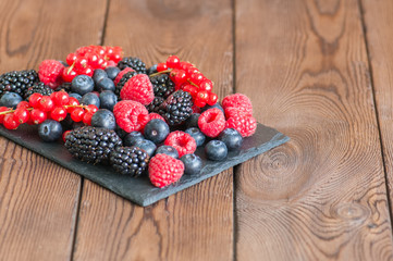 Mix of berries raspberries red currants blueberries and blackberries on black slate board. Wooden background.  Close up and copy space.