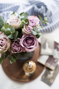 Pastel purple, mauve color fresh summer roses in vase in tray cl