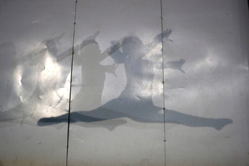 Shadows of a gymnast are cast on a wall during a training session in Santiago