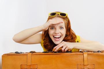frau mit koffer schaut in die ferne