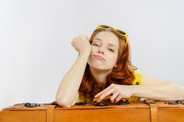 frau stützt sich auf einen koffer und sieht gelangweilt aus
