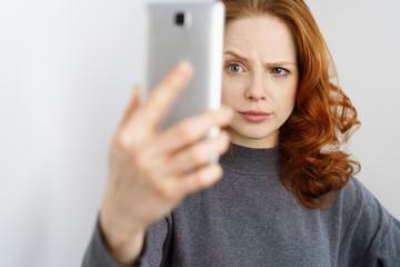 frau schaut mit ernstem blick auf ihr mobiltelefon