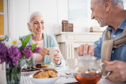 smiling grey haired couple having breakfast at home