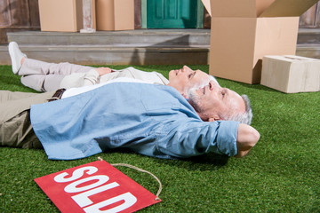 Happy senior couple lying on green grass between cardboard boxes and sold sign