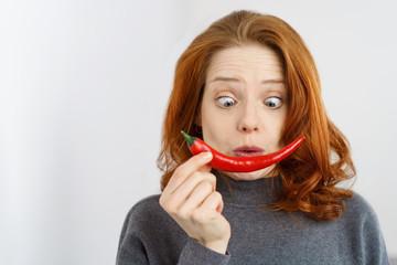 frau schaut ängstlich auf eine scharfe peperoni
