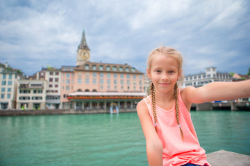 Adorable little girl taking selfie outdoors in european city. Closeup portrait of kid background of beautiful city