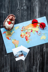 accessories for treveling with children, map and photos on dark woode background top view