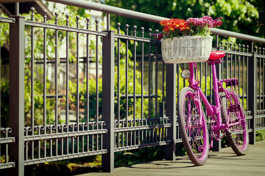 pink bike standing by metal barrier