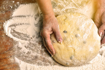 Hands of an elderly woman kneading yeast dough with raisins on wooden background