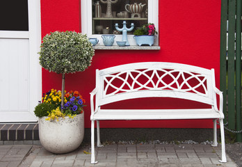White bench in front of red house