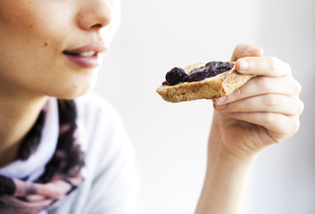 Young woman eating toast bread with jam