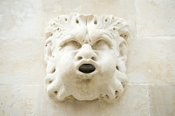 Stores à enrouleur Fontaine Close-up of the expressive face carved in stone with a mouth as a spigot for a fountain in Venice, Italy