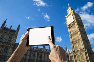 Hand touching screen of blank tablet in front of Big Ben and Westminster Palace in London under bright blue skies