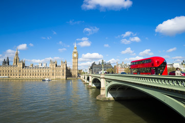 Puffy white clouds pass across bright blue sky in a scenic morning view of the Houses of Parliament at Westminster Palace from across the River Thames in London, England Wall mural