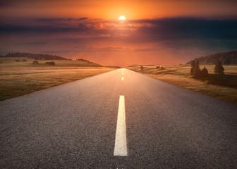 Empty road through mountain scenery at idyllic sunset