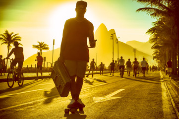 Silhouette of Brazilian man skating with boombox on the Ipanema beachfront in Rio de Janeiro, Brazil