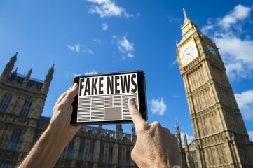 Reader scrolling through fake news stories on his tablet computer in front of the Houses of Parliament at Westminster Palace in London, England